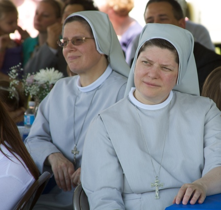 Two sisters dressed in light gray habits and veils